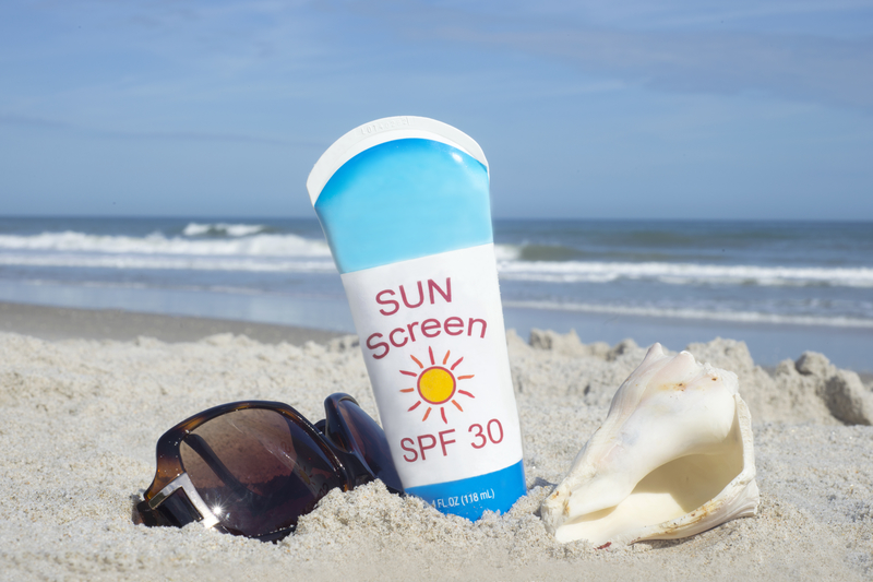 Sun screen bottle and sunglasses on a sandy beach - 10 Simple Sunburn Hacks to Soothe Your Skin